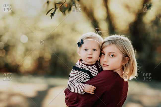 Portrait of a blonde girl holding her baby sister