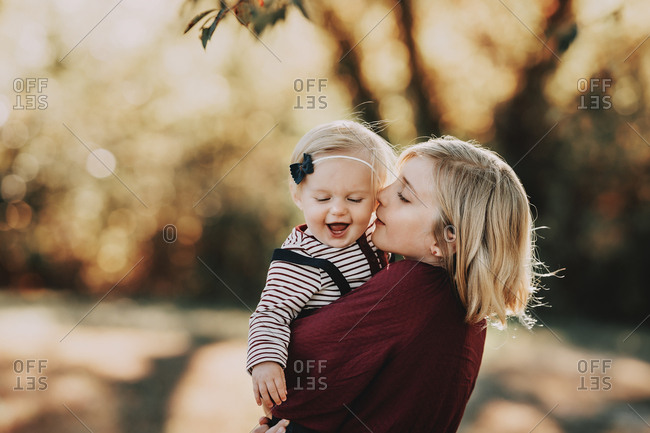 Blonde girl kissing baby sister's cheek