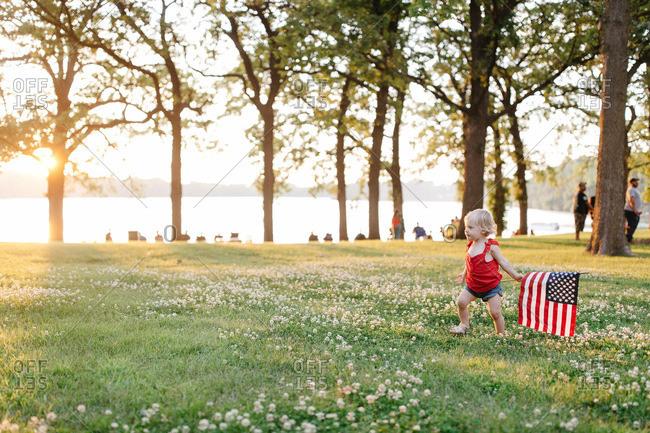 Little girl walking in field with American flag