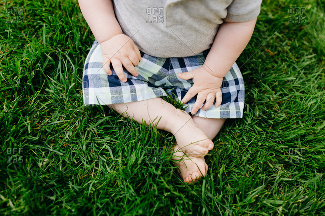 Overhead view of a barefoot toddler boy in the grass