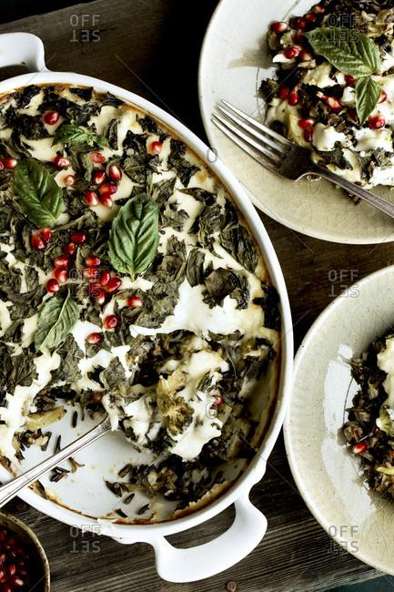 Cheesy broccoli wild rice casserole with crispy basil being served