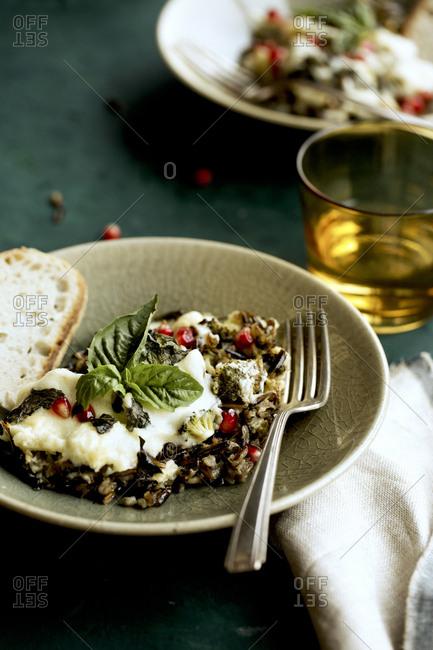 Close up of cheesy broccoli wild rice casserole with crispy basil