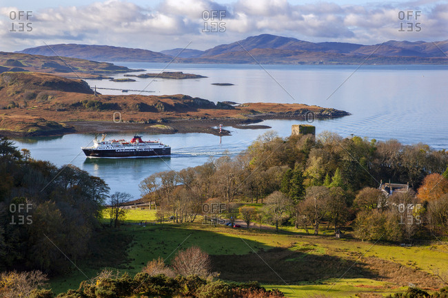 Argyll, Scotland - October 28, 2019: Autumn view of Ferry passing the Dunollie castle in Oban