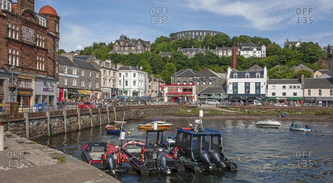 Argyll, Scotland - August 10, 2019: Summer scene from Oban's North Pier towards George St and McCaigs Tower
