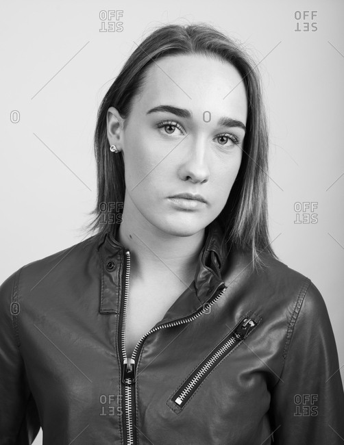 Close up black and white portrait of a young woman wearing a leather jacket