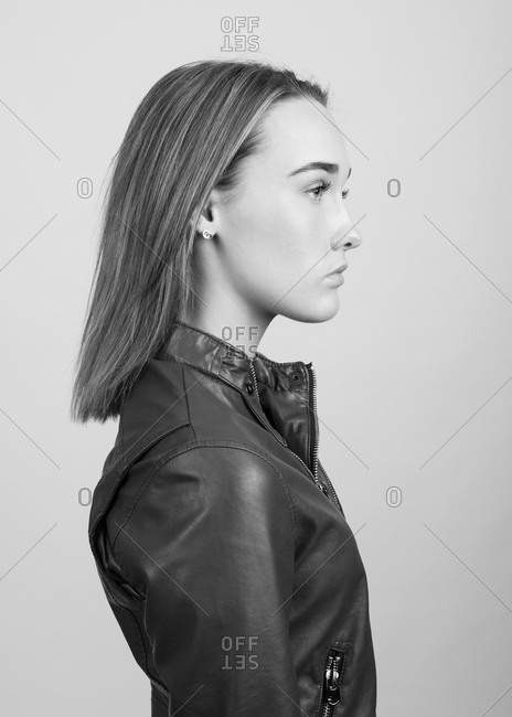 Profile portrait of a young woman wearing a leather jacket in black and white