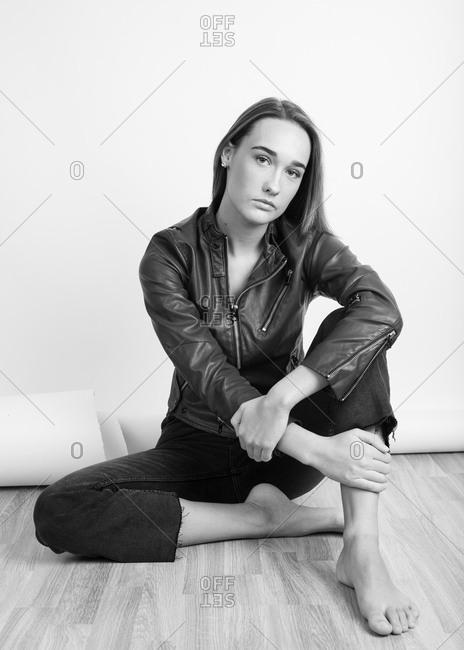 Black and white portrait of a barefoot young woman wearing a leather jacket and sitting on floor
