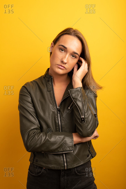 Portrait of a young woman wearing a leather jacket in front of yellow background