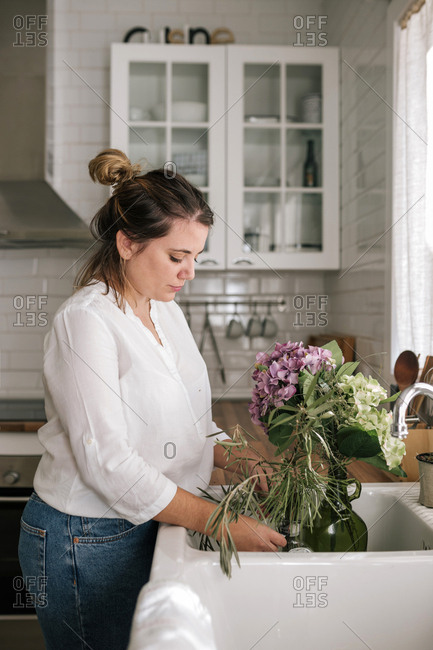 Young woman preparing a bouquet of flowers in the kitchen