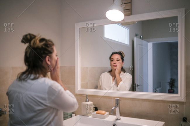 Young woman looking in the mirror in a bathroom