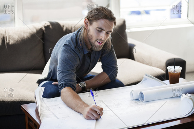 Businessman writing on blueprint in creative office
