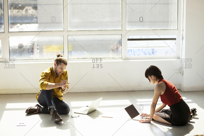 High angle view of business people using laptops on floor in creative office
