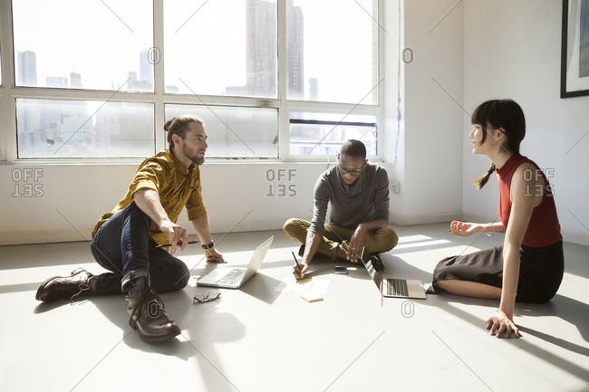 Business people discussing while sitting on floor at creative office