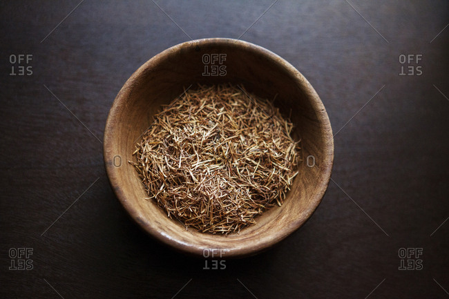 Overhead view of herbs in wooden bowl on table
