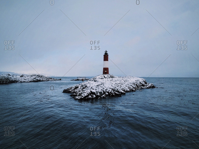 Lighthouse on rock formation amidst sea against sky during winter