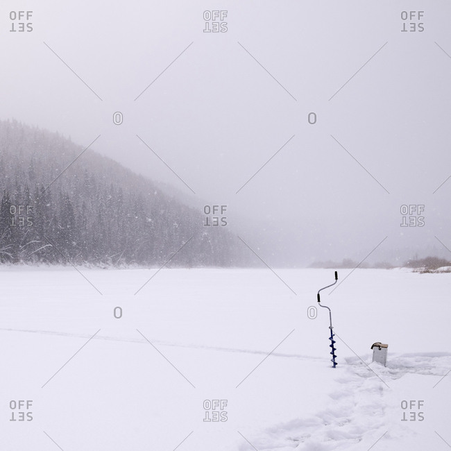 Ice auger on snow covered field during snowing