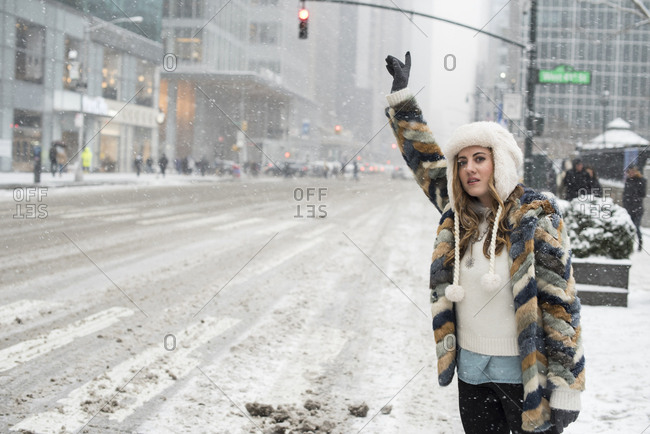 Woman hailing for taxi while standing on snow covered road in city