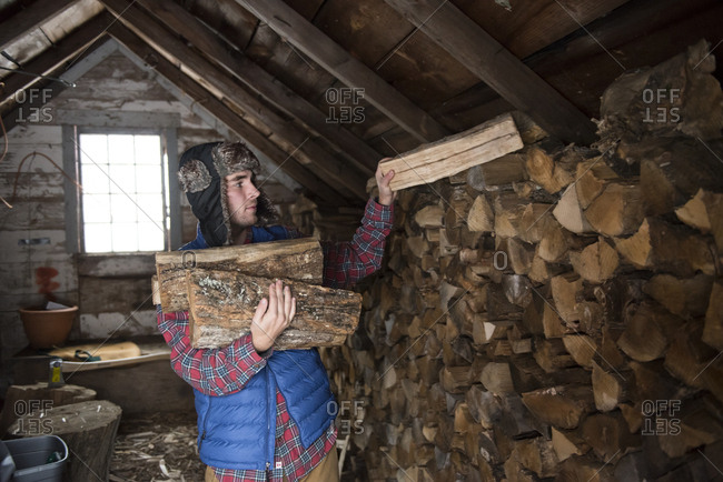 Man keeping firewood in workshop