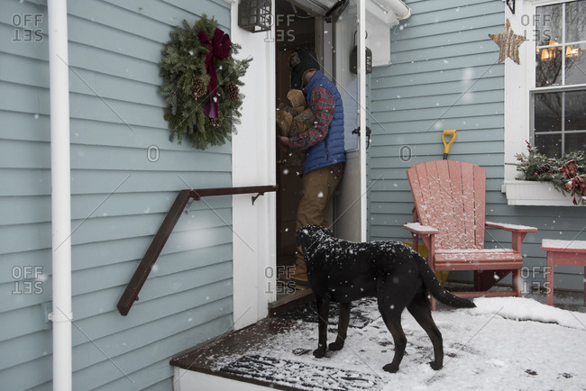 Man with firewood entering into house while dog standing at doorway