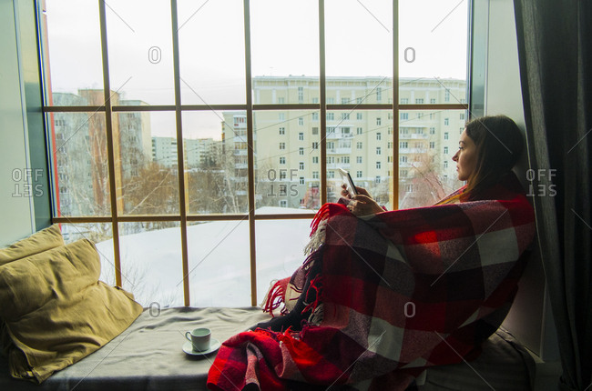 Woman wrapped in blanket while sitting on alcove window seat