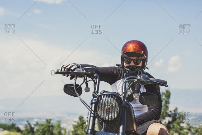 Portrait of biker sitting on cruiser motorcycle against sky