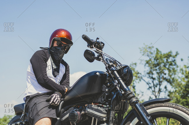 Low angle view of biker with cruiser motorcycle against sky