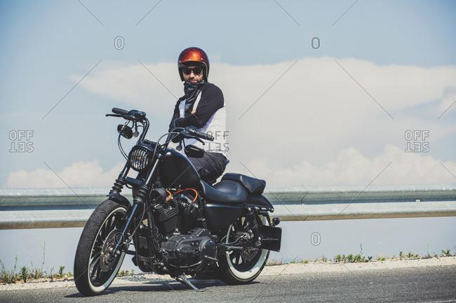 Biker standing by cruiser motorcycle on roadside against sky