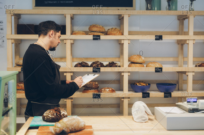 Side view of baker writing on clipboard while standing by shelves in bakery
