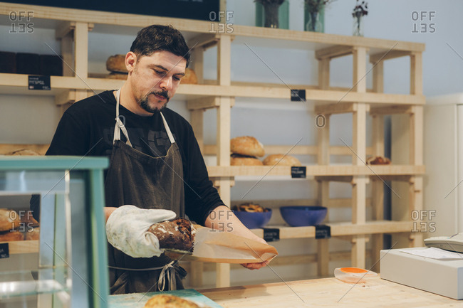 Bakery owner packing bread in paper bag while standing at counter