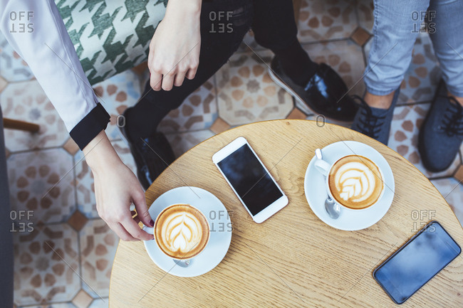Low section of businesswomen with coffee and mobile phones on table in cafe