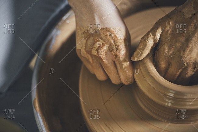 Overhead view of woman working on pottery wheel at workshop