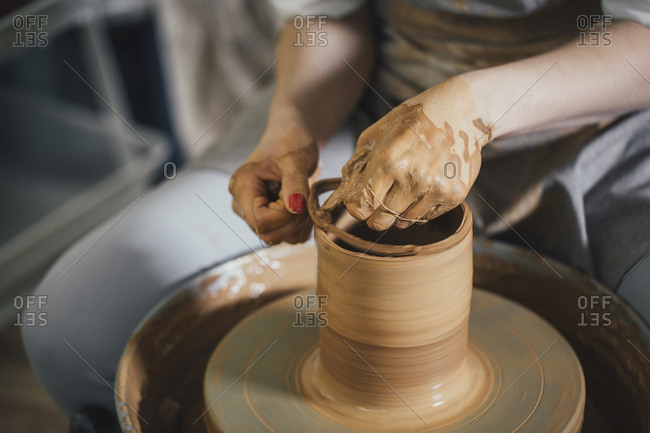 Midsection of female potter cutting clay on pottery wheel with thread at workshop