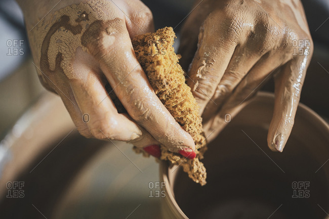 Cropped image of female potter scrubbing clay pot at workshop