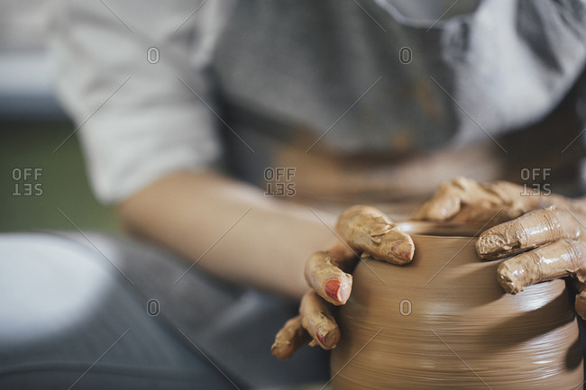 Midsection of woman shaping clay on spinning wheel at workshop