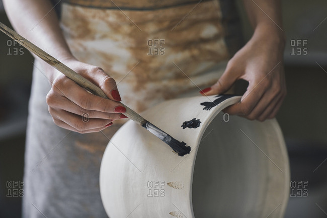 Midsection of female potter painting clay vase in workshop
