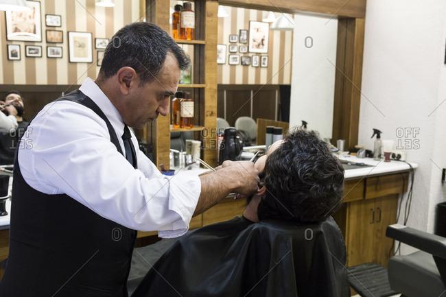 Barber cutting man's beard in shop