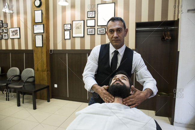 Barber doing facial massage to man in shop