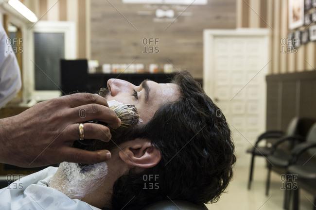 Cropped image of barber applying shaving cream on man's face