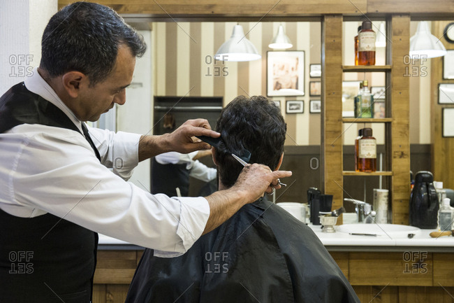 Side view of barber cutting man's hair in shop