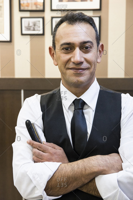 Portrait of smiling barber with razor blade in shop