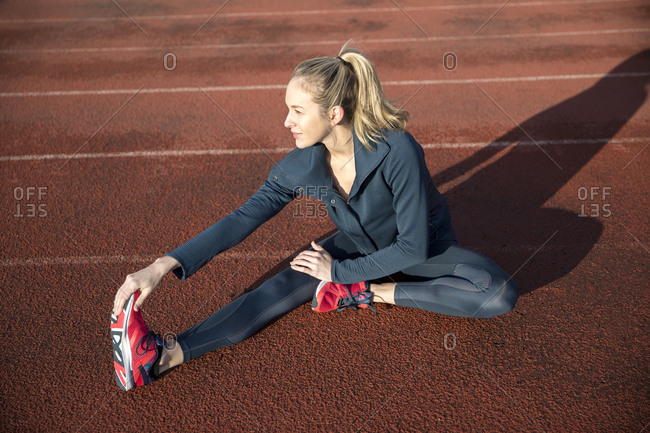 High angle view of female athlete exercising on sports track