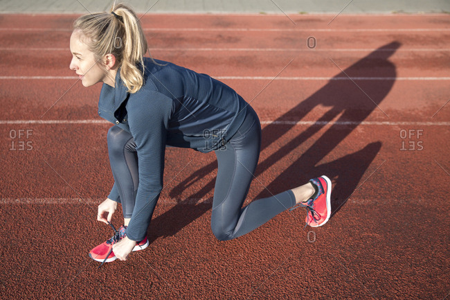 Side view of female athlete tying shoelace on sports track