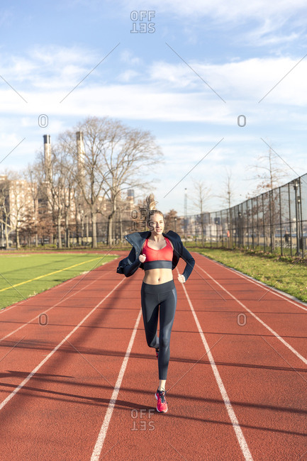 Athlete running on sports track against sky