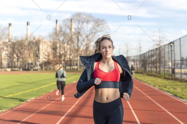 Female athlete running on sports track against sky