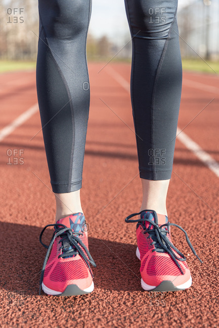 Low section of female athlete standing on sports track