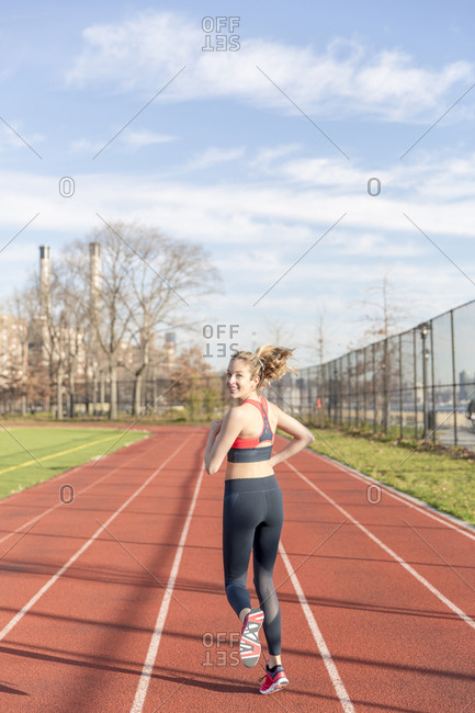 Portrait of athlete running on sports track against sky