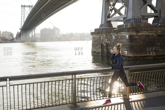 Athlete running on promenade by East River