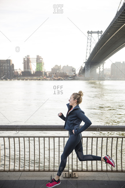 Side view of athlete running on promenade by East River