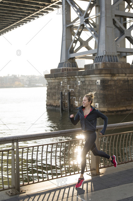 Confident athlete running on promenade by East River