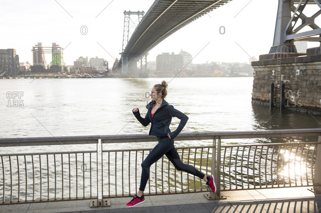 Side view of confident athlete running on promenade by East River